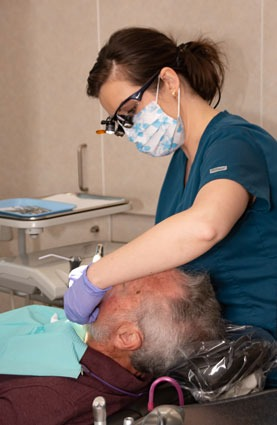 marcus dental examining a patients mouth - Dental Care Services